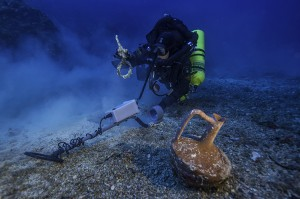 "Greek technical diver Alexandros Sotiriou discovers an intact ""lagynos"" ceramic table jug and a bronze rigging ring on the Antikythera Shipwreck. (Brett Seymour, Copyright: Return to Antikythera 2014)"